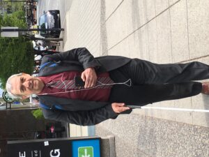 Man in suit walking along sidewalk with iPhone held in left hand at chest level. White cane pointed downward in right hand.